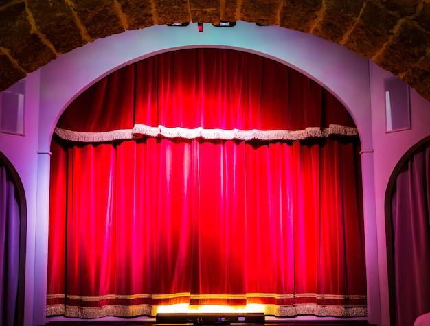 Uma cortina vermelha em um antigo e muito pequeno teatro italiano.