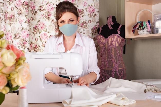 Uma costureira com uma máscara, uma pequena empresa