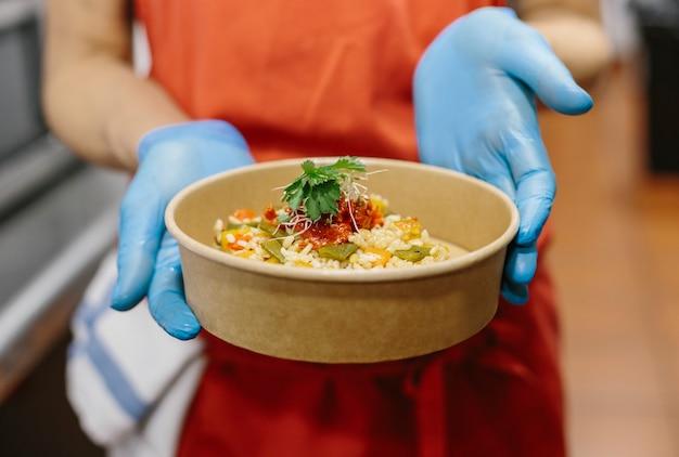 Uma cozinheira apresenta sua salada de arroz gourmet em um recipiente compostável para levar