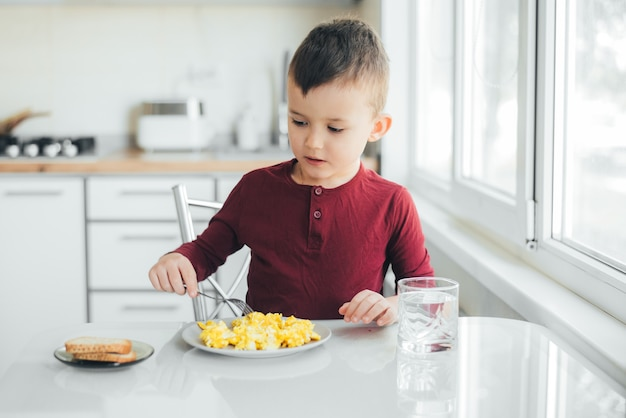 Uma criança à tarde em uma cozinha com luz branca em um suéter cor de vinho come uma omelete
