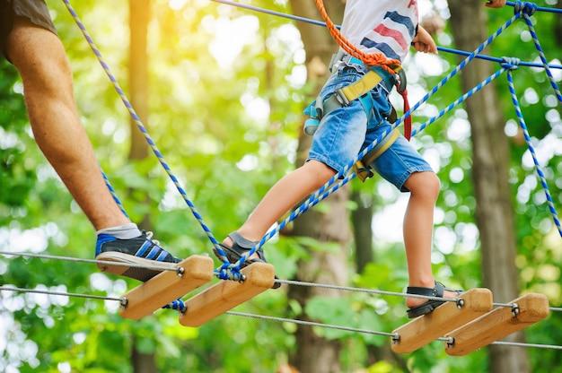 Uma criança acompanhada por um adulto se move no curso de cordas