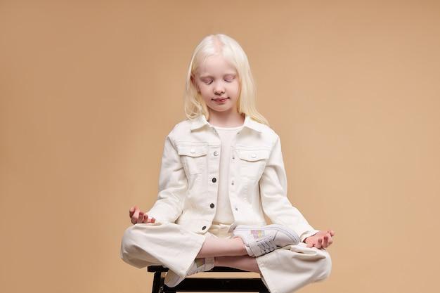 Uma criança albina alienígena incomum sentada em pose de ioga, meditando isolada