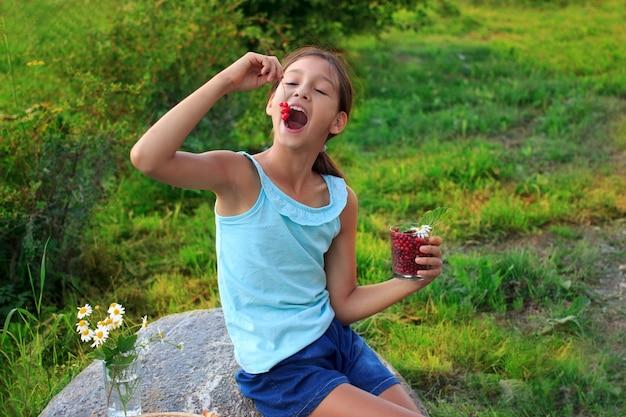 Uma criança alegre comendo groselha no jardim