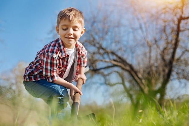 Uma criança alegre e sorridente escavando a terra com uma pá em um jardim familiar