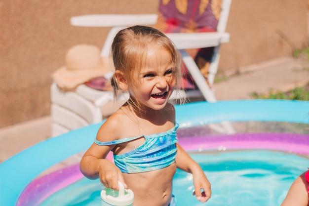Uma criança alegre em uma piscina inflável se banha no quintal em um maiô
