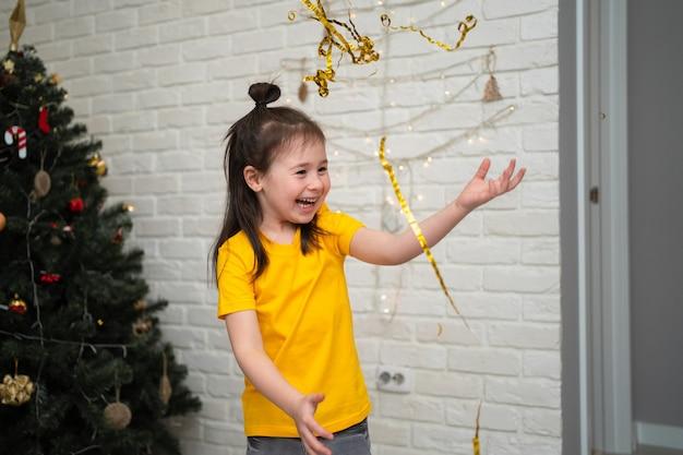 Uma criança alegre pega enfeites de natal em um feriado infantil brilhante uma criança em uma camiseta amarela pega uma serpentina