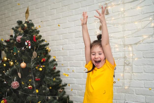 Uma criança alegre pega os enfeites. férias brilhantes para crianças. uma criança com uma camiseta amarela pega uma serpentina.