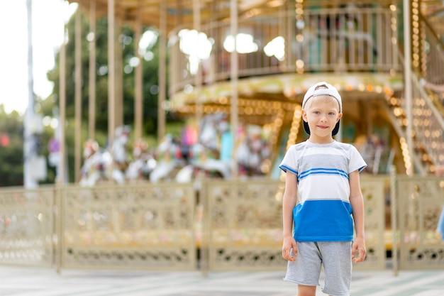 Uma criança alegre, um menino, caminha em um parque de diversões. estilo de vida infantil