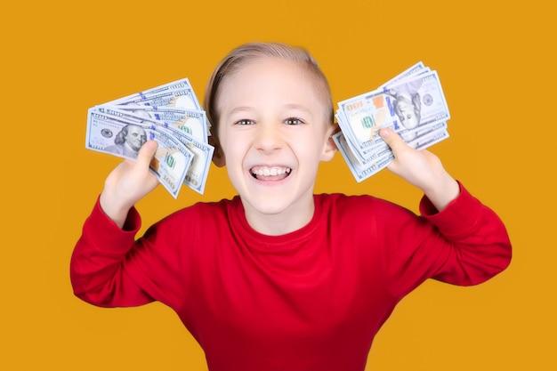 Uma criança alegre vestida de vermelho com um monte de notas de um dólar na frente do rosto