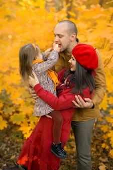 Uma criança alimenta seu pai com uma maçã enquanto está sentada nos braços de sua mãe
