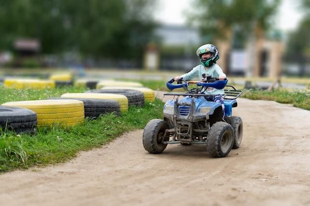 Uma criança anda de atv na pista