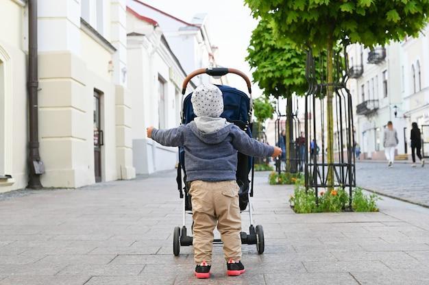 Uma criança anda pela cidade com um carrinho. vista traseira