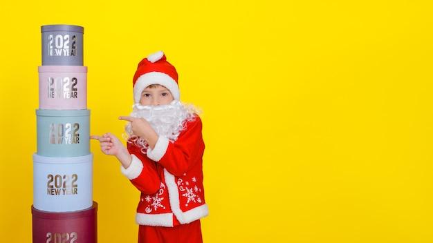 Uma criança aponta com o dedo indicador para uma torre feita de caixas de presente redondas com o ano novo de 2022