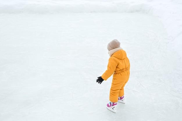 Uma criança aprende a patinar em um lago congelado. Foto Premium
