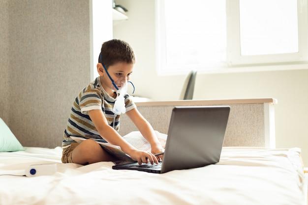 Uma criança aprende aulas em casa com uma máscara de oxigênio com um nibulizador, laptop e um livro