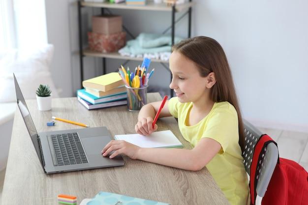 Uma criança aprende online em casa por meio de um laptop moderno na internet