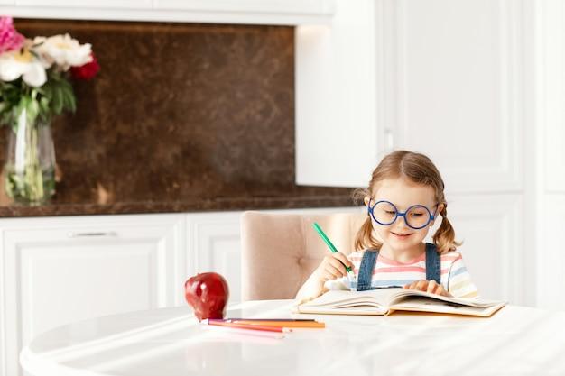 Uma criança aprendendo a escrever, fazendo a lição de casa, sentada na mesa, sozinha fazendo anotações desenhando lápis de cor