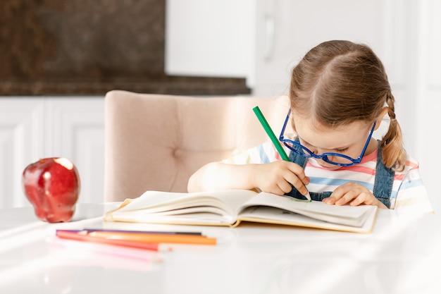 Uma criança aprendendo a escrever, fazendo a lição de casa, sentada na mesa, sozinha, fazendo anotações, desenhando lápis de cor Foto Premium