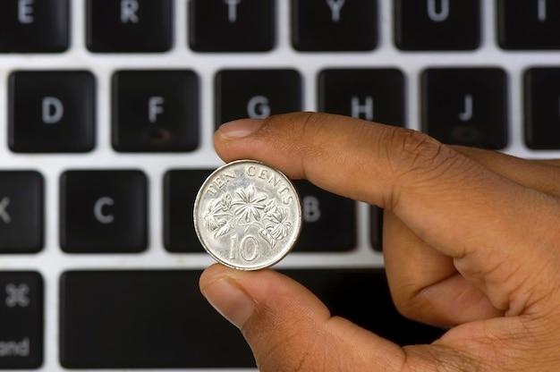 Uma criança asiática segurando uma moeda de cingapura de dez centavos com um fundo desfocado do teclado do computador