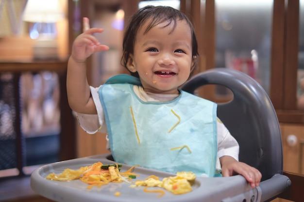 Uma criança asiática sorridente e feliz comendo com as mãos