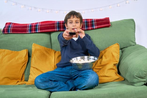 Uma criança assistindo tv no sofá e comendo pipoca em casa
