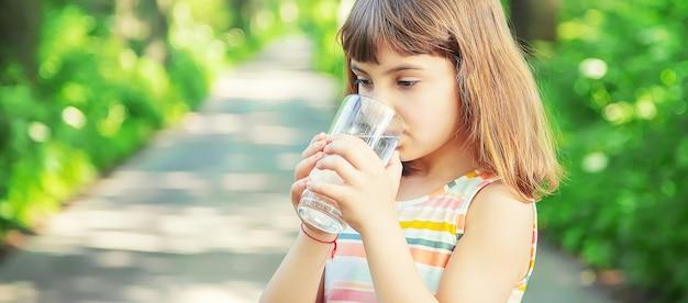 Uma criança bebe água de um copo na natureza