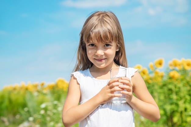 Uma criança bebe água no fundo do campo