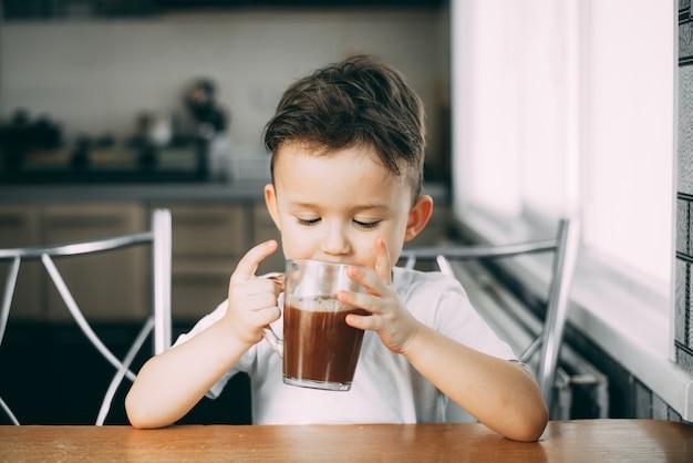 Uma criança bebe cacau na cozinha ou doce de chocolate quente à luz do dia