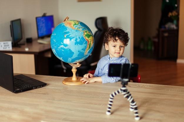 Uma criança blogueira grava um vídeo em um smartphone em um tripé que o menino posa em uma câmera de smartphone ...