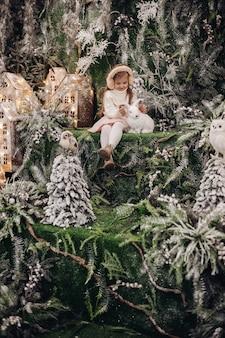 Uma criança bonita caucasiana com longos cabelos loiros sentada em uma atmosfera de natal com várias árvores decoradas ao seu redor e um coelhinho