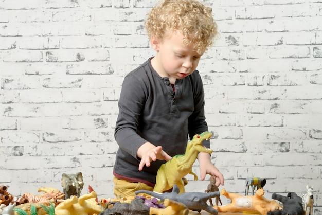 Uma criança brinca com animais brinquedos