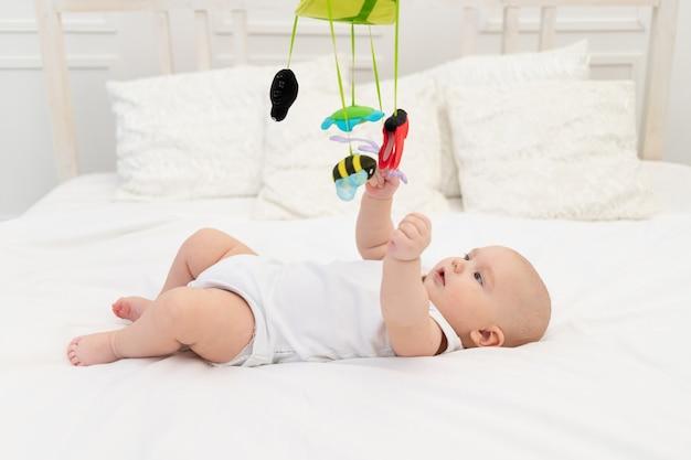 Uma criança brinca com um celular na cama do quarto das crianças