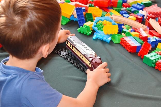 Uma criança brinca com um trem de brinquedo. construtor de desenvolvimento infantil.