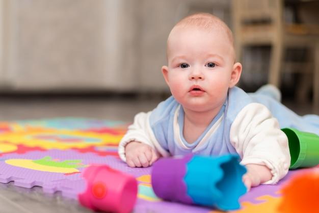 Uma criança brinca no chão. a criança está deitada de bruços no tapete com uma pirâmide.