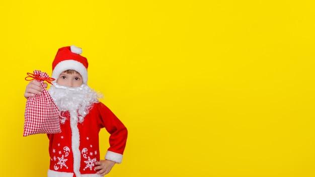 Uma criança caucasiana com roupas de papai noel e barba branca artificial mostra uma sacola de presentes
