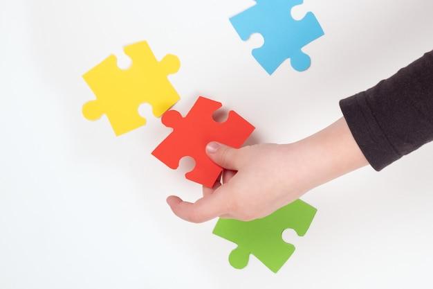 Uma criança com autismo coleciona quebra-cabeças, ensinando crianças.