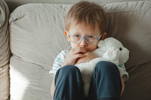 Uma criança com autismo de óculos sentada no sofá e triste