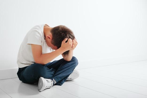 Uma criança com depressão está sentada no chão