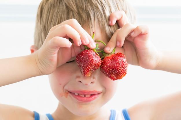 Uma criança com morangos. o garoto segura duas frutas vermelhas perto dos olhos