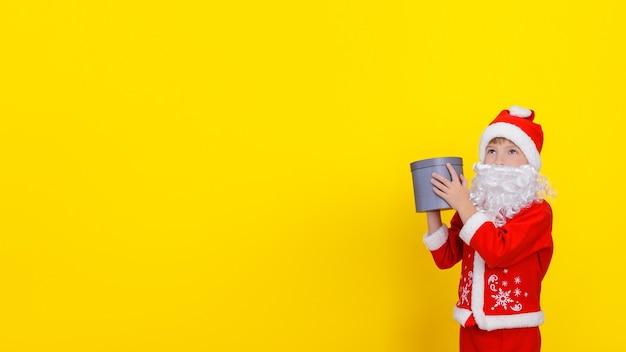 Uma criança com roupas de papai noel e barba artificial segura uma caixa redonda de presente nas mãos