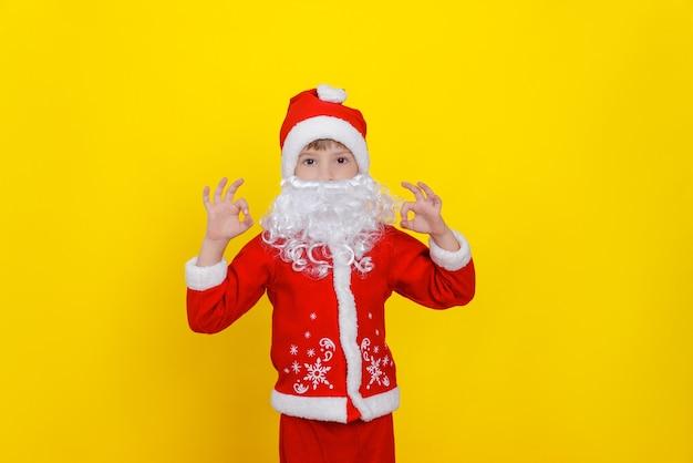 Uma criança com roupas de papai noel e uma barba artificial faz um gesto de ok com as duas mãos