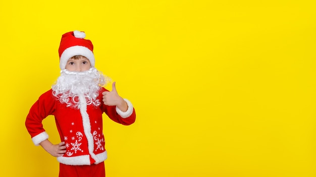 Uma criança com roupas de papai noel e uma barba artificial faz um gesto de polegar para cima com as mãos