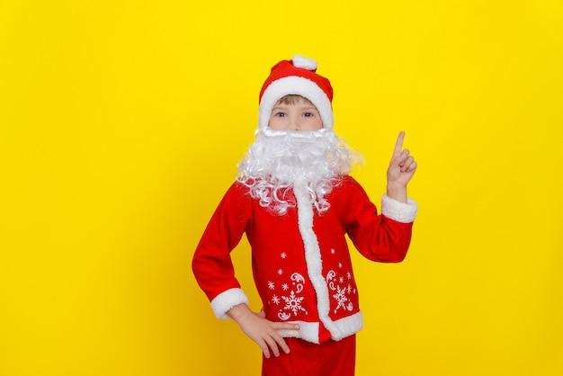 Uma criança com roupas de papai noel e uma barba artificial fazendo um gesto com a mão com o dedo indicador para cima
