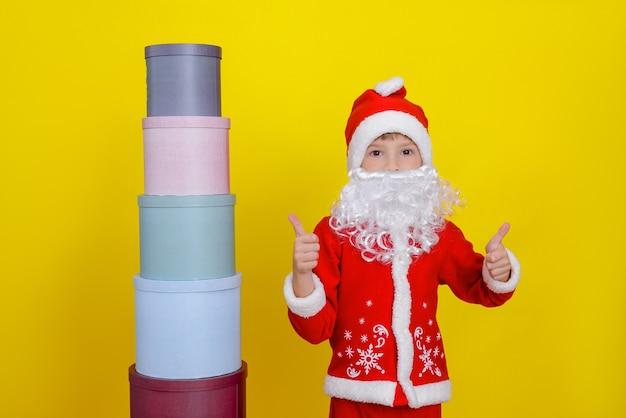 Uma criança com roupas de papai noel mostra um gesto de positivo ao lado de uma torre de caixas de presente redondas