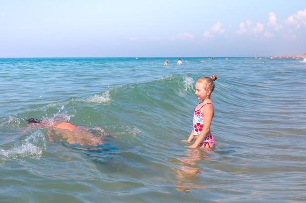 Uma criança com seus pais nadando nas ondas do mar o pai mergulhou nas aventuras do mar de água