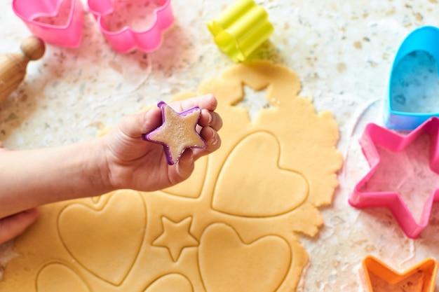 Uma criança com sua mãe faz biscoitos, estende a massa e usa formulários para fazer biscoitos.
