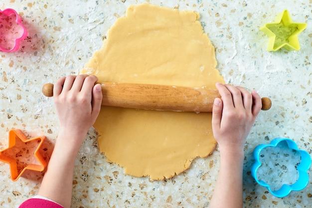 Uma criança com sua mãe faz biscoitos, estende a massa e usa moldes para fazer biscoitos