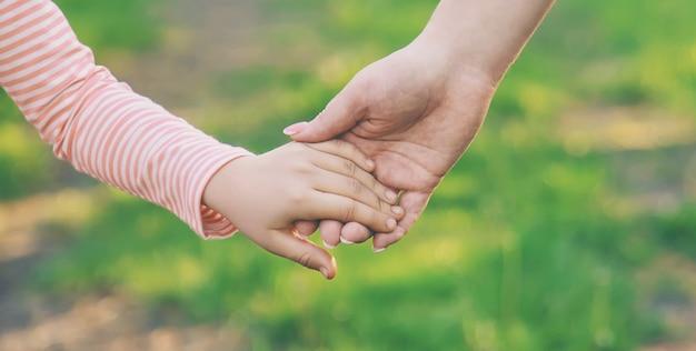 Uma criança com sua mãe passa pela mão