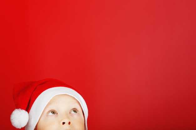 Uma criança com um chapéu de papai noel em um fundo vermelho ergue os olhos da parte inferior do quadro.
