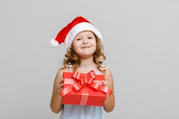 Uma criança com um chapéu de papai noel está segurando uma caixa de presente vermelha